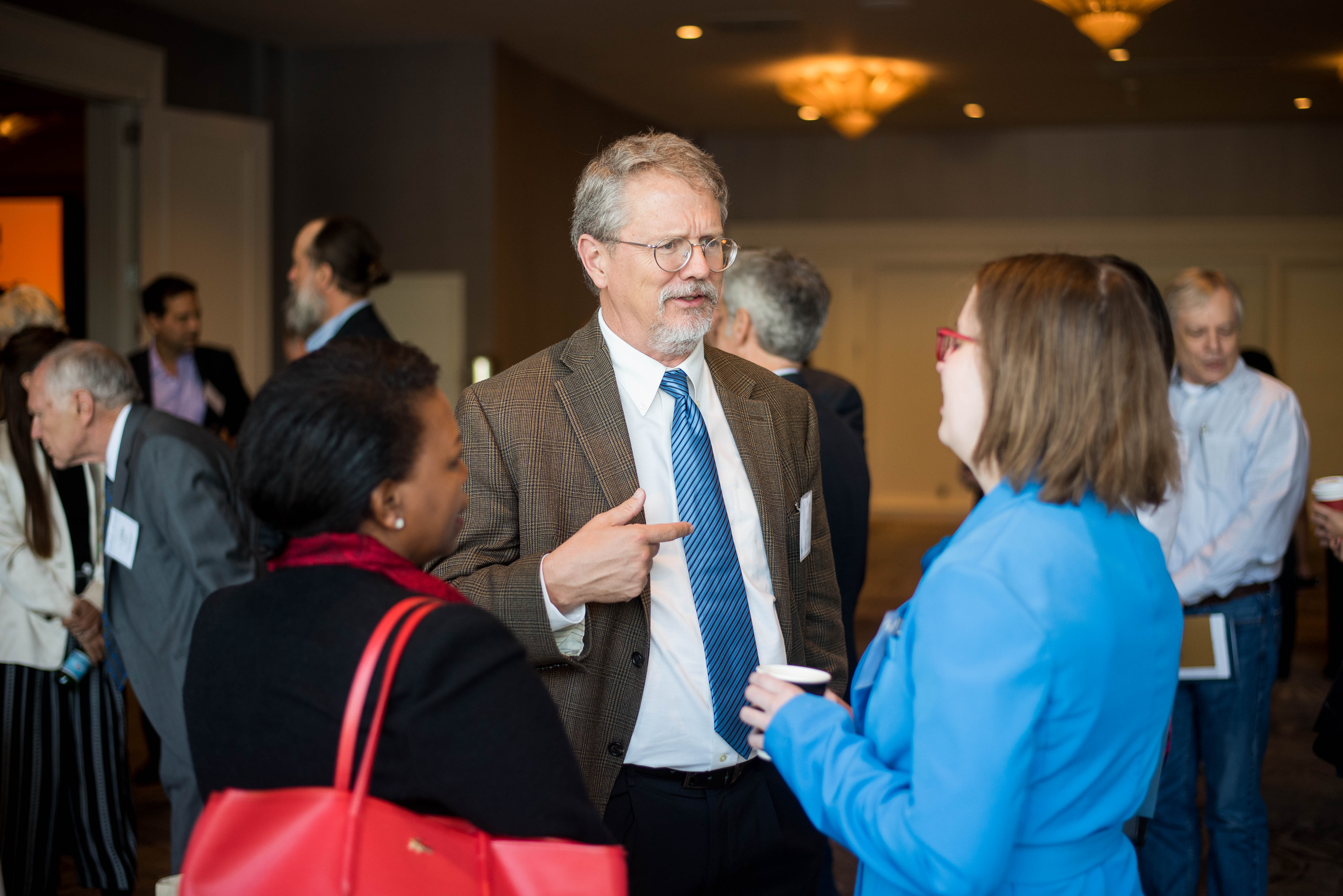 Three people speaking with one another at PolicyWest 2019